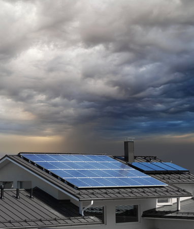 Solar panel system on house roof, stormy rain clouds approaching