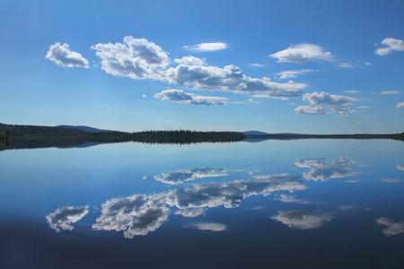 Calm blue Lake Äkäsjärvi reflects white cloud in Finnish Lapland