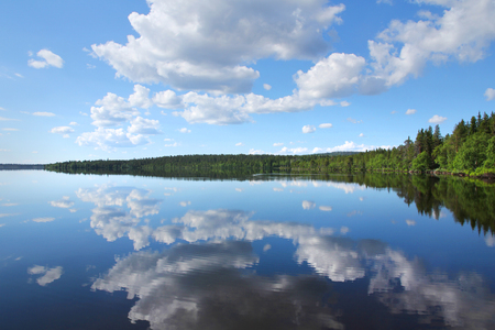 Perfect Finnish lake scenery with white clouds reflecting from calm clear water 版權商用圖片