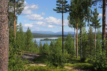 Beautiful Finnish Lapland summer lake scenery and hiking trail, with Pallastunturi fells on the horizon