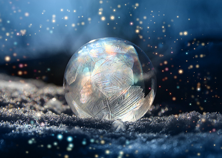 Magical color glitter frostball on cold winter snow, crystal formations, dark background 版權商用圖片