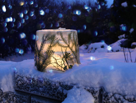 Frozen ice lantern with spruce twigs in snow, lit with candle light 版權商用圖片