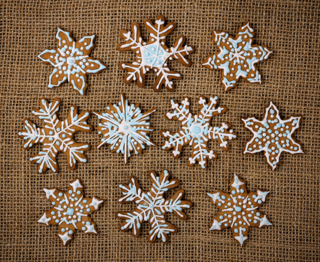 Decorated snowflake Christmas gingerbread cookies on brown burlap canvas background 版權商用圖片
