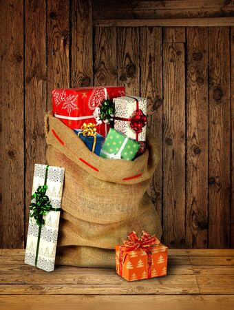 Santas present sack with gift boxes against old rough wooden plank wall