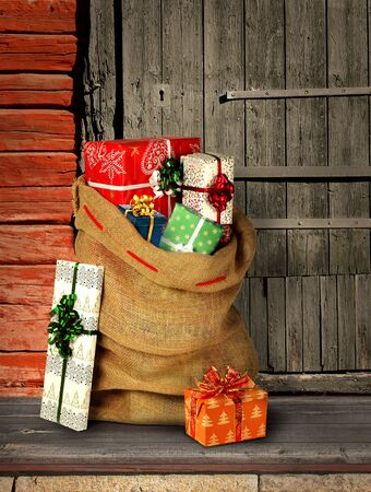 Santas present sack with gift boxes on rough wooden log cabin entrance