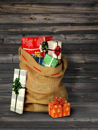Santas present sack with gift boxes against old grey wooden plank wall