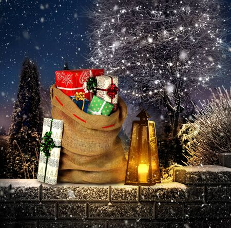 Santas presente saco con cajas de regalo en jardín de invierno al aire libre con linterna y vela