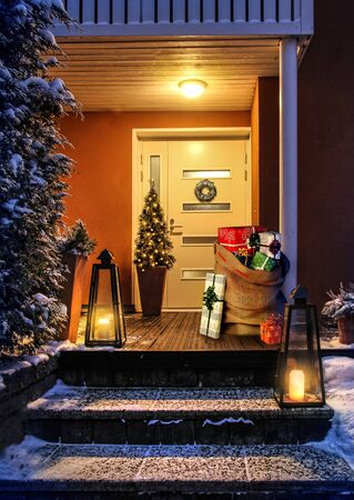 Welcome Christmas - house entrance snowy steps and door with decoration. Santas present sack with gift boxes