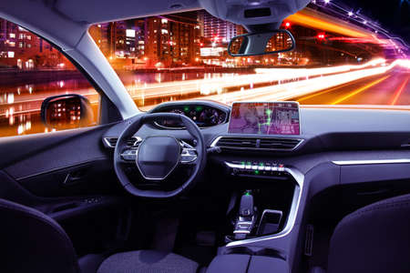 Modern car cockpit interior in night traffic, navigating or autonomous driving concept