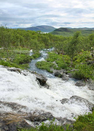 Streamlet waterfall from Lake Tsahkal in Northern Lapland wilderness, fells on the background