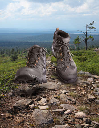 Hiking boots walking onstony wilderness path background, outdoor trekking activity concept