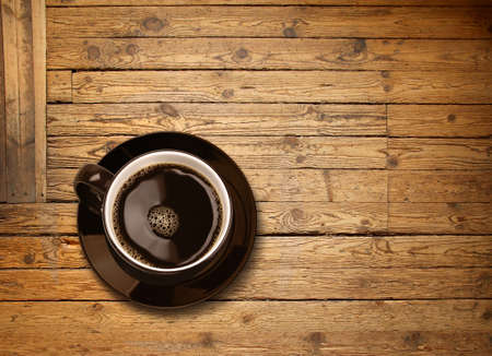 Cup of black coffee on old weathered wooden plank table background, top view