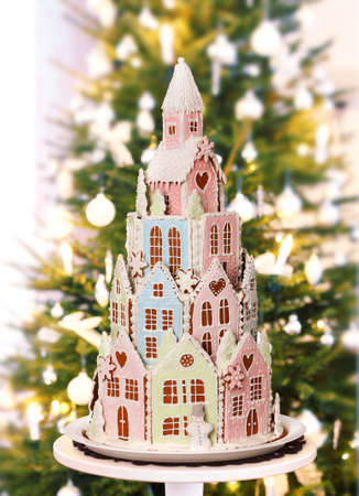 Gingerbread castle with real fir Christmas tree on home living room background