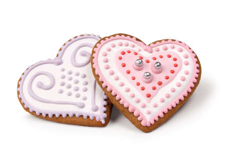 Two heart shaped decorated Christmas gingerbreads isolated on white