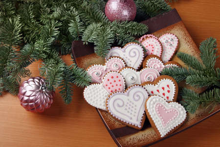 Christmas gingerbreads with icing, on spruce branches background