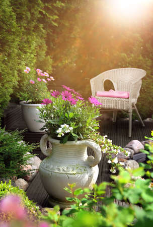 Peaceful, sunny and warm hideaway garden patio feeling with flowers in clay pots and wicker chair
