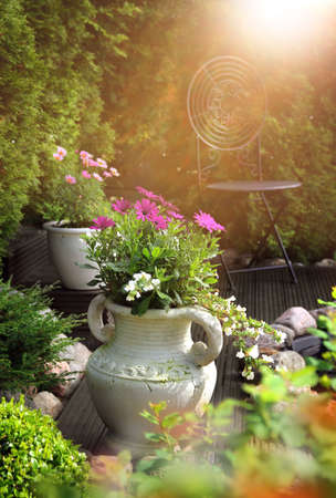 Peaceful, sunny and warm hideaway garden patio feeling with flowers in clay pots