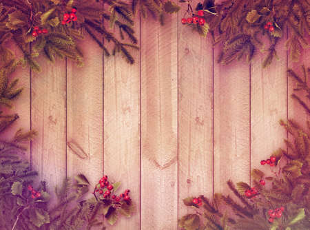 Christmas tree branches and red berries on wooden plank wall old postcard style background