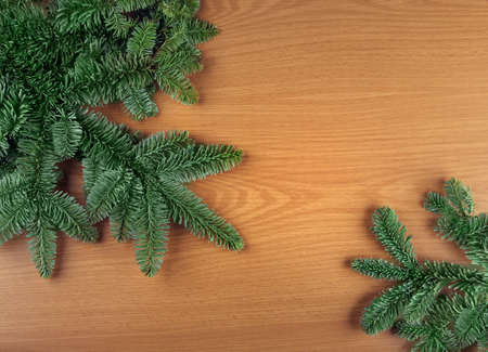 Green Christmas fir tree spruce branches on wooden background