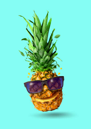 Funny tropical jumping pineapple fruit with sunglasses, holiday concept, isolated on turquoise background