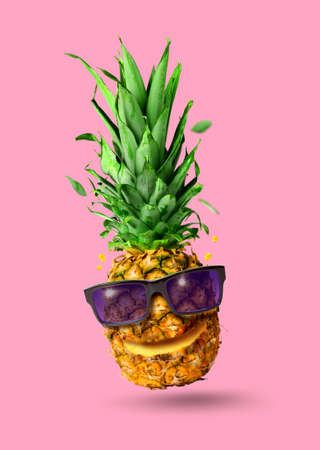 Funny tropical jumping pineapple fruit with sunglasses, holiday concept, isolated on pink background Standard-Bild