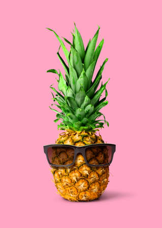 Fresh tropical pineapple fruit with sunglasses, isolated on pink background, holiday concept