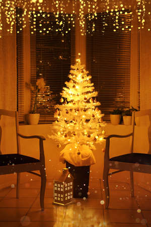 Illuminated white Christmas tree in front of a bay window, with decoration and string lights