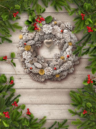 Green Christmas tree branches, red hawthorn berries and white cone wreath on grey wooden vertical plank doorbackground