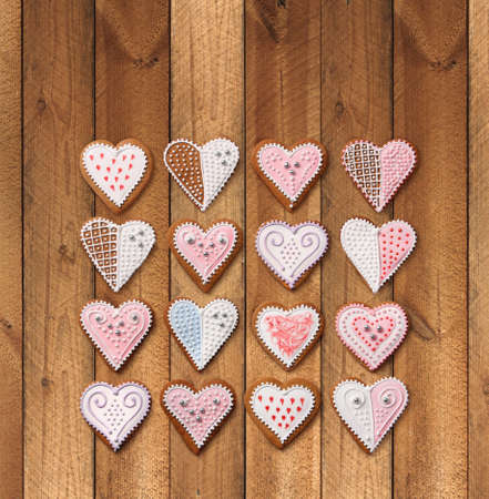 Sweet Christmas heart shaped gingerbread cookies collection with colorful sugar icing decoration, on old wooden background