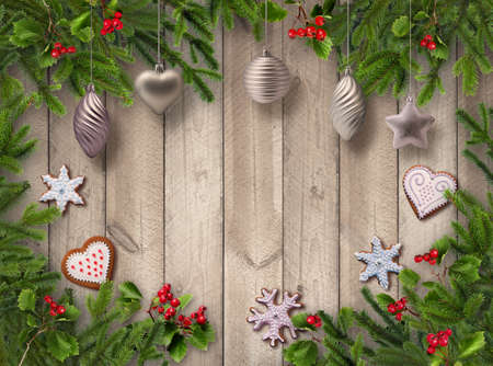 Green Christmas tree branches, red berries, gingerbread cookies and silver decoration balls on wooden vertical plank wall background