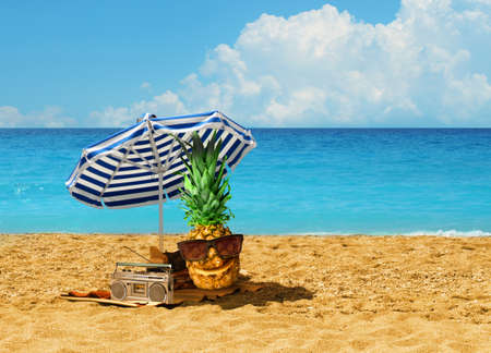 Happy pineapple character having summer holiday under blue-white umbrella on hot sandy beach by turquoise blue ocean