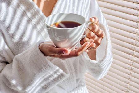 Close up of female hands holding white cup of tea at spa salon, standing near window blinds, she's wearing white robe