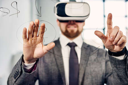 Mid age businessman in VR glasses working at the office
