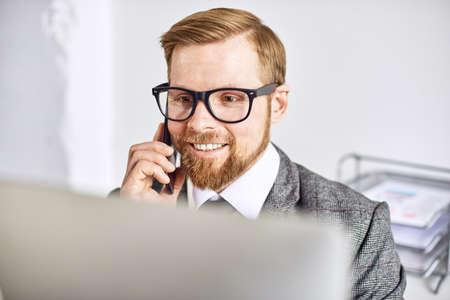 Zakenman van middelbare leeftijd die op de computer op kantoor werkt Stockfoto