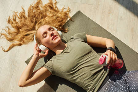 Girl in sports wear lies on the floor. Stock Photo