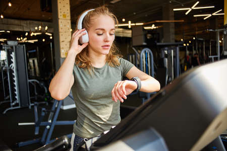 Girl in headphones running on the treadmill.