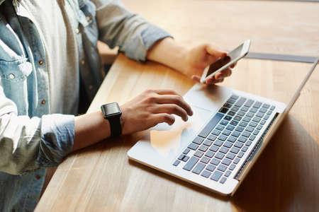 Le jeune homme travaille sur l'ordinateur portable dans le café.