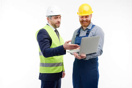 Engineer and foreman are discussing a new project looking at a laptop