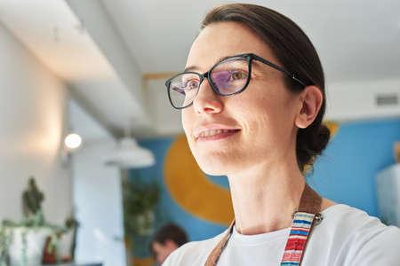 Beautiful barista in glasses drinks coffee and smiles. 版權商用圖片