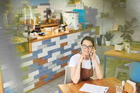 Barista in the apron writing in the notepad. 版權商用圖片