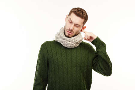 Man in a green sweater has his ears aching.