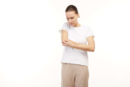 Woman in white t-shirt itching her arm.