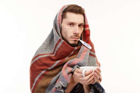 Ill man in white t-shirt covered with a big scarf takes medicine on the white background. Stock fotó