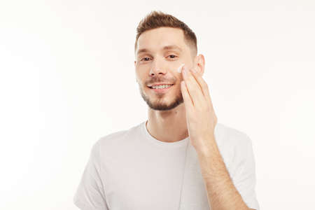 Man touches his face after shaving it some time before.