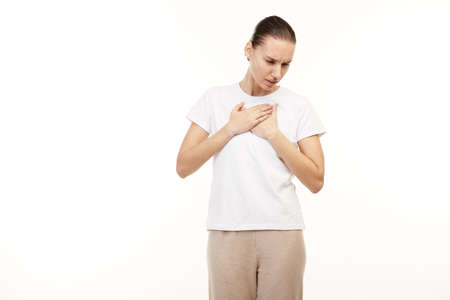 Woman in white t-shirt having itching troat pains.