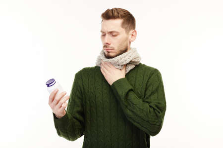 Man in a green sweater takes his prescribed meds.