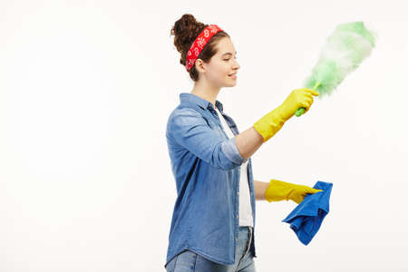 Pretty woman in work-wear uses dust cleaning supplies not facing the camera. Banque d'images