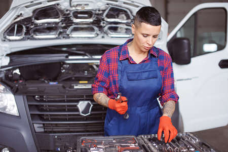 Woman works at the car repair checking whether she has all the instruments.