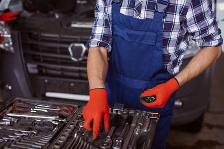 Close up of a man choosing an appropriate instrument to fix the car engine by himself.