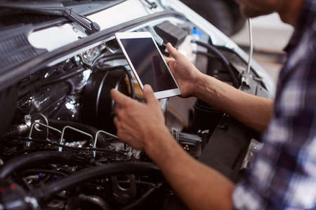 Close up of a man using his tablet to know how to fix car engine because the case is unusual. Foto de archivo